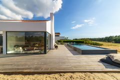 Modern house with garden swimming pool and wooden deck. Modern white house with garden swimming pool and wooden deck stock photography
