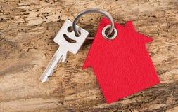 Modern house key on keyring. With model house Royalty Free Stock Photo
