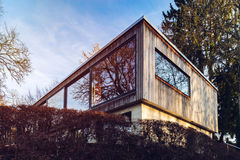 Modern house with long glass wall, mirror glazing, sunset. Fribourg, Swiss stock photo