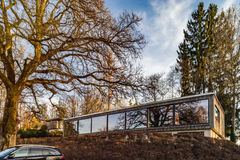 Modern house with long glass wall, mirror glazing, sunset. Fribourg, Swiss royalty free stock photo