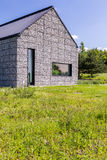 Modern house in the meadow. With pebble stone walls and narrow windows Stock Photography