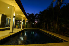 Modern house with pool at dusk royalty free stock images