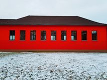 Red House in the snow. Modern house with red façade in winter stock images