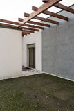 Modern house in renovation. Modern white and grey house in renovation with wooden pergola stock image