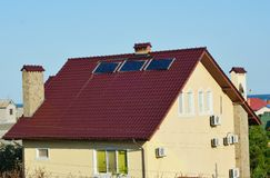 Modern house roof with solar water heater panels and air conditioner compressors for energy efficiency stock photo