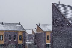 Modern house rooftops covered in snow during snowy weather, Modern dutch architecture background royalty free stock photography