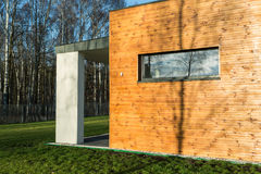 Modern house with wooden walls. Big modern house with wooden walls and big green garden. In the back of house little stone porch Stock Images