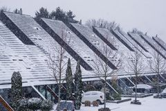 Modern houses with pointy rooftops in a dutch neighborhood during winter season, snowy weather in a village of the Netherlands. A modern houses with pointy stock photos