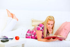 Modern housewife laying on couch and reading book Stock Photos