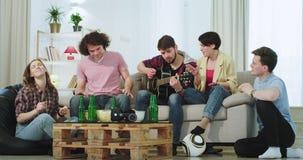 In modern huis heeft een groep mooie mensen prettijd die samen op een gitaar zingen en in een ruime woonkamer dacing stock videobeelden