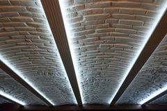 Modern huisbinnenland met verlicht baksteenplafond Stock Fotografie