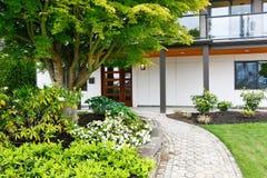 Modern husentryway med den konkreta gångbanan och trevliga landskapet som desing Arkivfoto