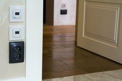 Modern husinre med varma golvkontrollantpaneler på väggen, träparketten och vitdörren royaltyfri foto
