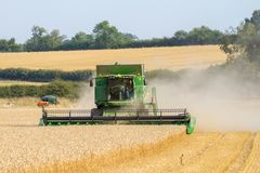 Modern 9780i cts john deere combine harvester cutting crops corn wheat barley working golden field. With tractor and trailer stock photos