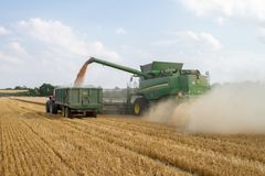 Modern 9780i cts john deere combine harvester cutting crops corn wheat barley working golden field Stock Image