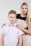 Modern i en beige klänning som kramar sonen Arkivfoton