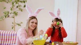 Modern i kaninöron dekorerar påskägg, och dottern står bredvid och rymmer påskägg som ögon lager videofilmer