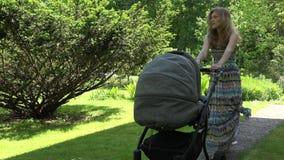 Modern i klänningförsök att överföra behandla som ett barn för att sova i sittvagn i trädgård 4K lager videofilmer