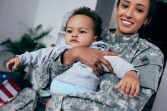 Modern i militär likformig med behandla som ett barn Royaltyfri Foto