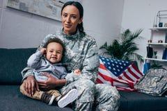 Modern i militär likformig med behandla som ett barn pojken Arkivfoto