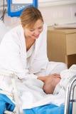 Modern i sjukhus med nyfött behandla som ett barn Arkivbild