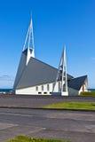 Modern Iceland Church on bright blue sky background. Vertical shot Stock Photos