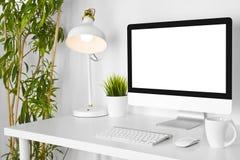Modern idérik märkes- arbetsplats med skrivborddatoren på den vita tabellen Arkivfoton