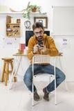 Modern idérik man med smartphonen på workspace. royaltyfri foto