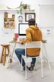 Modern idérik man som arbetar på workspace. arkivfoton