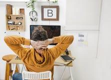 Modern idérik man som kopplar av på workspace. royaltyfri foto