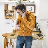 Modern idérik man som talar med smartphonen på workspace. royaltyfri fotografi