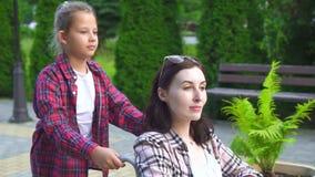 Modern inaktiverade i en rullstol och en dotter på en gå i parkera långsam mo lager videofilmer