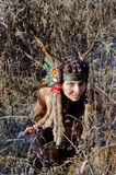 Modern Indian-style girl in a horned and feathered hat. Dancing tribal and shamanic ritual dances Royalty Free Stock Photos
