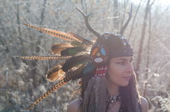 Modern Indian-style girl in a horned and feathered hat. Dancing tribal and shamanic ritual dances Royalty Free Stock Photo