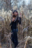Modern Indian-style girl in a horned and feathered hat. Wearing jeans and black sweater Royalty Free Stock Photography
