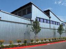 Modern industrial building with steel exterior. An industrial type building with tilted roof and windows. Has a corrogated steel exterior stock photo