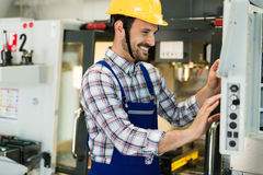 Modern industrial machine operator working in factory stock image