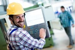 Modern industrial machine operator working in factory royalty free stock image