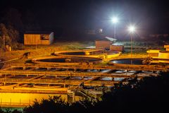 Modern industrial wastewater treatment plant at night. Aerial view of sewage purification tanks stock images