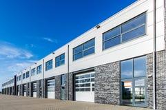 Modern industribyggnad med päfyllningsdörrar och blå himmel Royaltyfri Bild