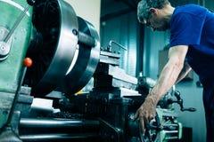 Modern industriell maskinoperatör som arbetar i fabrik Arkivfoton