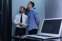 Modern innovative laptop standing on the table. Electronic device. Modern innovative laptop lying on the table with two professional male technicians standing in Royalty Free Stock Image