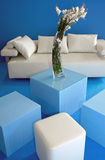 Modern interior. Combination of luxurious leather white sofa with tabouret with blue sponges in box-shape, coffy table covered with glass, and  2 sponge tabouret Royalty Free Stock Photography