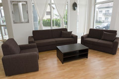 Modern interior. Dark brown sofa with club table is nice contrast in this white colored room Royalty Free Stock Photo
