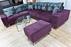 Modern interior. Purple corner sofa with tabouret and glass coffee table Royalty Free Stock Photos