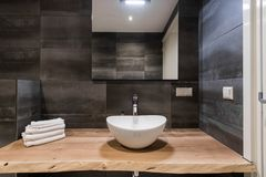 Modern interior of the bathroom. The washbasin is made of white massive shell on the table of wood. Minimalism and Stock Images