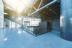 Modern interior. Corridor in the modern office building, with escalators, stairs, glass walls and reflective floor, natural light and flare Royalty Free Stock Photo