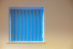 Modern interior design. Blue vertical blinds over window on yell Stock Photography