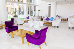 Modern interior design of a hotel lobby. Fragment of the lobby of the five stars luxury hotel. Lounge area. Interior design.purple and white chairs Royalty Free Stock Images