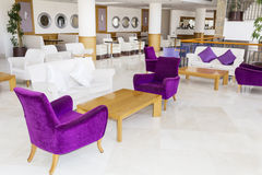Modern interior design of a hotel lobby. Fragment of the lobby of the five stars luxury hotel. Lounge area. Interior design.purple and white chairs Royalty Free Stock Photos